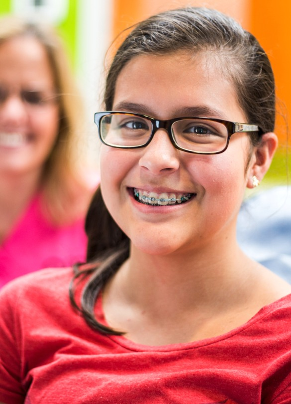 patient red shirt glasses and braces with team in g Ossi Orthodontics Jacksonville and St. Augustine Florida Orthodontist